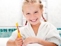 Auftragende Zähne des kleinen Mädchens lizenzfreie stockbilder