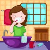 Auftragende Zähne des Mädchens im Badezimmer lizenzfreie abbildung