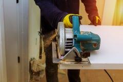Auftragnehmer, der eine elektrische S?ge verwendet, um T?rbretter auf dem Bau eines neuen Hauses zu schneiden lizenzfreie stockbilder