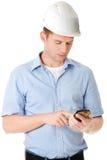 Auftragnehmer im Hardhat unter Verwendung seines Handys lizenzfreie stockfotos