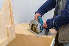 Auftragnehmer schneidet den Countertop für Wannenmöbel auf der Küche unter Verwendung der elektrischen Säge stockfoto