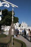 Aufwändige Glocke mit den Touristen, die Wat Rong Khun, Chiang Rai alias der weiße Tempel im Hintergrund bewundern stockfotografie
