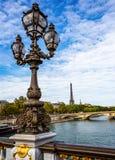 Aufwändige Lampe auf der Alexander III.-Brücke mit dem Eiffelturm im Hintergrund in Paris lizenzfreie stockfotos