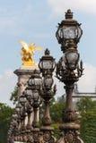 Aufwändige Laternenpfähle auf Brücke Alexander-III in Paris Stockfotografie