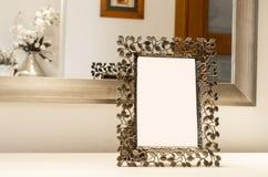 Aufwändiger Bilderrahmen auf der weißen Tabelle Reflexion im Spiegel Bla stockbild
