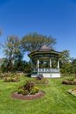 Aufwändiger Gazebo im grünen Garten unter blauem Himmel Stockbilder