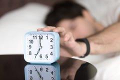 Aufwachen des Mannes in der tragenden Manschette des Betts, die Wecker abstellt lizenzfreie stockfotografie