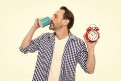 Aufwachen erneuert und angezogen Trinkender Kaffee des b?rtigen reifen Mannes mit Uhr in der Hand Reifer Mann mit Wecker stockbilder