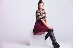 Aufwerfende Modefrau beim Sitzen Stockbild