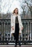 Aufwerfende schöne junge Blondine in voller Länge, die auf dem Frühlingsstadtpark in der warmen Kleidung stehen Kalte Jahreszeitl Lizenzfreies Stockfoto