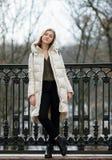 Aufwerfende schöne junge Blondine in voller Länge, die auf dem Frühlingsstadtpark in der warmen Kleidung stehen Kalte Jahreszeitl Stockfoto