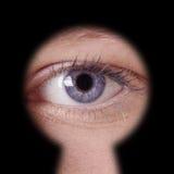 Auge, das durch Schlüsselloch schaut Stockbild