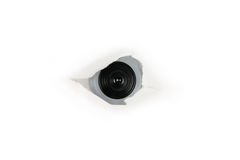 Auge des Spions, Web-Nocken hinter einem Papierloch lizenzfreies stockfoto