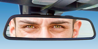 Augen in einem Autospiegel Stockfotos