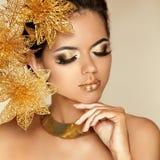 Augen-Make-up. Schönes Mädchen mit goldenen Blumen. Schönheit vorbildliches Wom Stockfoto