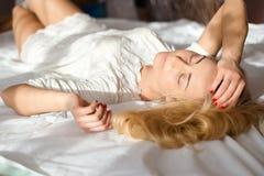 Augen schlossen das attraktive zarte schöne sexy blonde schlafende oder Entspannungslügen des Mädchens der jungen Frau in Lichtst Lizenzfreies Stockbild