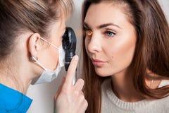 Augenarzt überprüft die Augen unter Verwendung eines Augengerätes Stockfotos