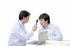 Augenarzt, der Ophthalmoskop bei der Untersuchung des männlichen Patienten verwendet stockfotos