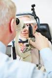 Augenarzt, der Spaltlampe verwendet Stockfotografie