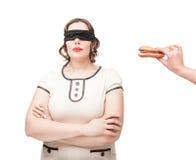 Augenbinde plus die Größenfrau, die mit Hamburger temptating ist Stockfoto