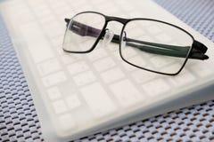 Augenglas auf dem Tisch gesetzt auf Computertastatur stockfotos