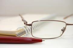 Augengläser und eine Feder auf Blatt Stockfotografie