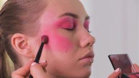 Augenmaskenbildner, der Lidschattenpulver anwendet und mit Federn versieht Vorbildliches Gesicht der Schönheit Nahaufnahme stock video