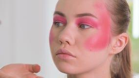 Augenmaskenbildner, der Lidschattenpulver anwendet und mit Federn versieht Vorbildliches Gesicht der Schönheit Nahaufnahme stock footage