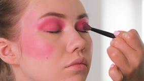 Augenmaskenbildner, der Lidschattenpulver anwendet und mit Federn versieht Vorbildliches Gesicht der Schönheit Nahaufnahme stock video footage