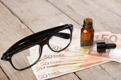 Augenpflegekonzept - Lesebrille, Augentropfen und Geld Stockfotografie