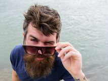 Augenschutzkonzept Mann mit Bart und dem Schnurrbart trägt Sonnenbrille, Wasseroberfläche auf Hintergrund Hippie auf dem Blinzeln Lizenzfreies Stockbild