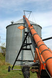 Auger and Grain Bin During Harvest. Orange augur and silver grain bin during Iowa harvest season Stock Photography
