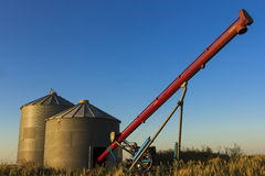 Auger and Grain Bins. Pair of grain bins and an auger in the middle of a field Royalty Free Stock Image
