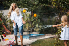 Ð'aughter watering mother from hose. Bath in the yard with mother stock photography