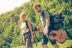Augmentant de jeunes ajouter au sac à dos de guitare extérieur Photographie stock