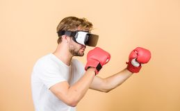 Augmented 3D world. Man boxer virtual reality headset simulation. Cyber coach online training. Explore cyber space. Cyber sportsman boxing gloves. Man play royalty free stock image