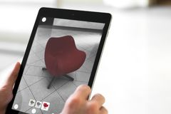 Augmented reality app - placing furniture in AR space. Augmented reality application - man placing furniture in AR space holding a tablet stock images