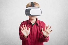 Augmented reality, children and entertainment concept. Small child in virtual headset enjoys beautiful and exciting pictures, stra. Tches hands, imagines Royalty Free Stock Image