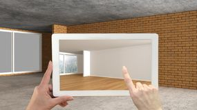 Augmented reality concept. Hand holding tablet with AR application used to simulate furniture and design products in an interior. Construction site, empty stock photography