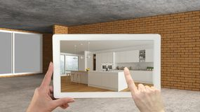 Augmented reality concept. Hand holding tablet with AR application used to simulate furniture and design products in an interior. Construction site, modern stock photography