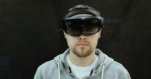 Augmented Reality Glasses. Young adult Caucasian man using holographic augmented reality glasses. Game development. Young man with holographic glasses stock footage