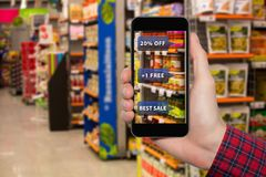 Augmented reality in marketing. Phone in hand, on screen information about prices and sales in food store stock photography