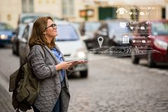 Augmented reality in marketing. Woman traveler with phone. Navigation on the projection of the display stock image