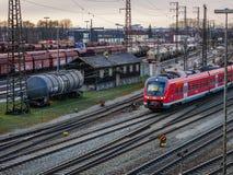 Augsburg Tyskland - mars 03, 2018: Rött regionalt drev från den tyska järnvägservicen Deutsche Bahn på stänger i royaltyfri foto