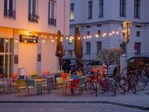 Augsburski, Niemcy, Maj - 5, 2019: Plenerowy arragement z kolorowymi krzesłami, stołami i światłami od prętowego Beim Weissen, obrazy stock