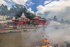 18. August 2014 - Begräbnis- Scheiterhaufen im Bagmati-Fluss in Kathmandu Stockbilder