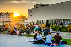 8 August, 2015, Bexhill, England, crowds gather for film screening. Crowds gather at sunset for an outdoor, summer screening of a film on the white wall at the stock images