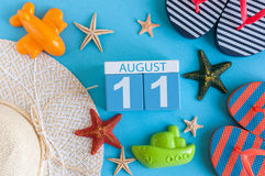 11. August Bild des vom 11. August Kalenders mit Sommerstrandzubehör und Reisendausstattung auf Hintergrund Baum auf dem Gebiet Lizenzfreie Stockbilder