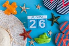 26. August Bild des vom 26. August Kalenders mit Sommerstrandzubehör und Reisendausstattung auf Hintergrund Baum auf dem Gebiet Lizenzfreie Stockfotografie