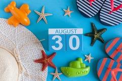 30. August Bild des vom 30. August Kalenders mit Sommerstrandzubehör und Reisendausstattung auf Hintergrund Baum auf dem Gebiet Stockfotografie